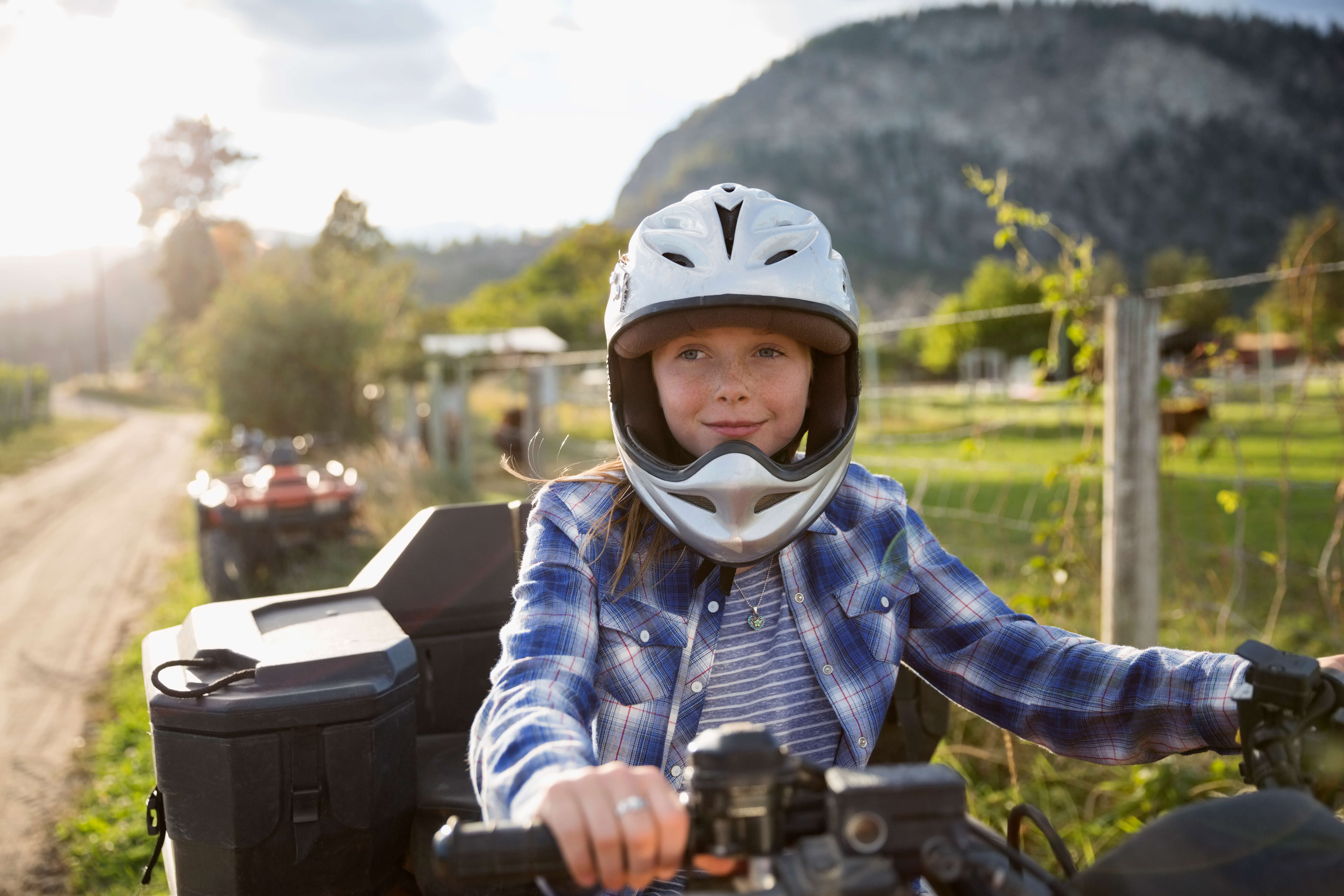 Smiling girl wearing helmet driving ATV on rural farm